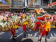 "19 FEBRUARY 2015 - BANGKOK, THAILAND: Chinese dragon dancers wait to perform for Chinese New Year at a business on Yaowarat Road in Bangkok. 2015 is the Year of Goat in the Chinese zodiac. The Goat is the eighth sign in Chinese astrology and ""8"" is considered to be a lucky number. It symbolizes wisdom, fortune and prosperity. Ethnic Chinese make up nearly 15% of the Thai population. Chinese New Year (also called Tet or Lunar New Year) is widely celebrated in Thailand, especially in urban areas that have large Chinese populations.    PHOTO BY JACK KURTZ"