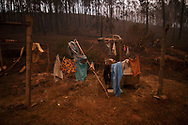 LEIRIA, PORTUGAL - JUNE 18:  Clothes are hanging for drying next to a burned car after a wildfire took dozens of lives on June 18, 2017 near Castanheira de Pera, in Leiria district, Portugal. On Saturday night, a forest fire became uncontrollable in the Leiria district, killing at least 62 people and leaving many injured. Some of the victims died inside their cars as they tried to flee the area.  (Photo by Pablo Blazquez Dominguez/Getty Images)