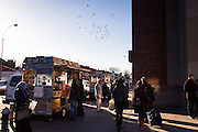 Indian food trucks and passersby at the corner of Broadway and 73rd Street, across from Diversity Plaza and the entrance to the 74th Street subway station.