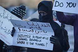 © London News Pictures.Calais, France. 07/03/16. Refugees stand in silent protest as French police enter the 'Jungle' camp to begin the second week of the demolition. French authorities are evicting and demolishing the southern half of the Calais 'Jungle' camp, which charities estimate to contain 3,500 people. . Photo credit: Rob Pinney/LNP