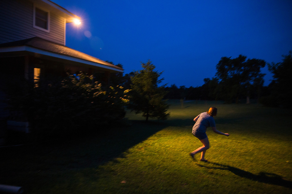 A young lady chases fireflies during the summer as night falls in the south.
