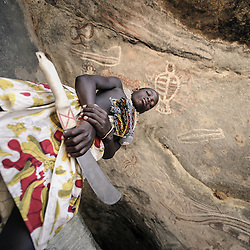 [PT] Fotografia de um Mucubal adolescente posando para a foto, fingindo que é o guardião das pinturas rupestres que se encontam nesta caverna no deserto do Namibe. Província do Namibe, Angola | [EN] A foto of a teenage boy from the Mucubal tribe posing for a photograph and pretending to be the guardian of the old rock paintings on the wall of this cave in the Namibe Desert in Angola. Namibe, Angola