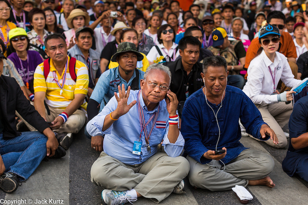 12 MAY 2014 - BANGKOK, THAILAND: SUTHEP THAUGSUBAN makes a phone call while sitting in Phichai Road near the Parliament building in Bangkok. Several thousand protestors with the People's Democratic Reform Committee (PDRC) blocked access to the Thai Parliament building in Bangkok as a part of their continuing anti-government protests. The Parliament is not currently in session and was dissolved by former Prime Minister Yingluck Shinawatra but the Senate is in session. The protestors are demanding that the Senate dissolve the current Pheu Thai caretaker government and appoint a new Prime Minister and cabinet. Members of the Senate leadership met with Suthep Thaugsuban Monday to discuss the impasse.   PHOTO BY JACK KURTZ