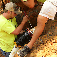 Seth Johnson tightens the screws to secure the compression fitting to a new section of water line in Saltillo.