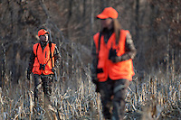 MALE AND FEMALE HUNTER WEARING BLAZE ORANGE WALKING TOGETHER