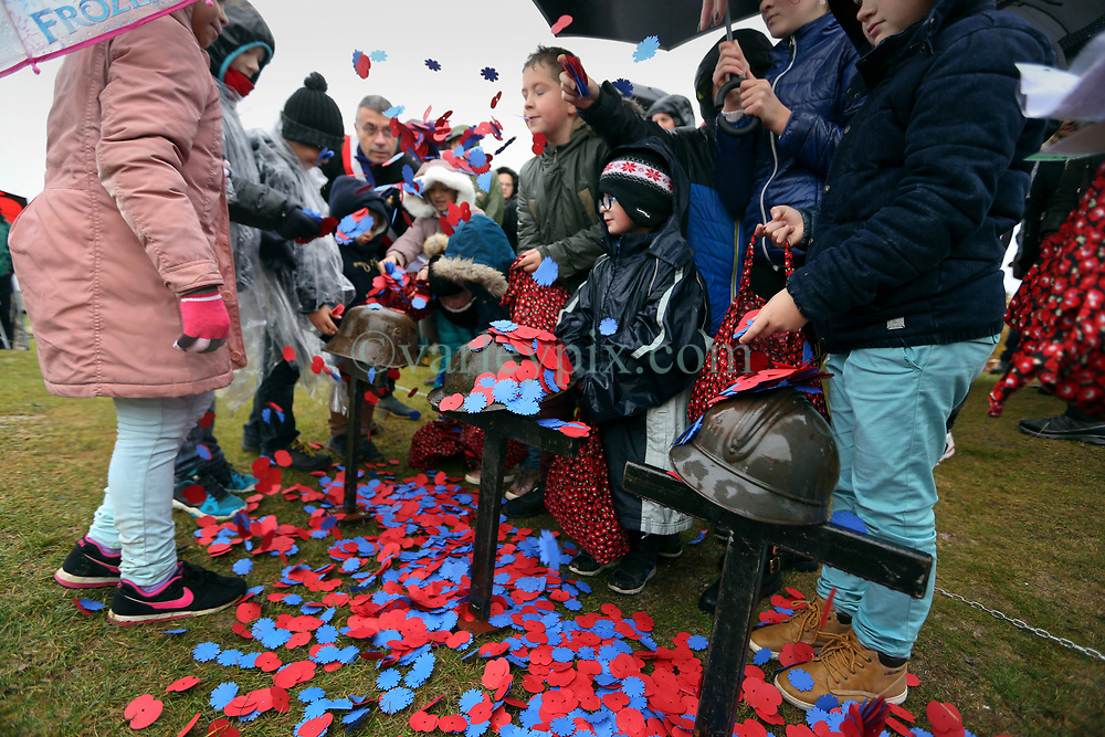 11 November 2018. Lochnagar Crater, La Boisselle, Somme, France. <br /> <br /> Local school children throw petals on the helmets of fallen soldiers. Gathered in the pouring rain, those who perished in the Great War are remembered by British and French civilians on the 100th anniversary of the Great War. <br /> <br /> Lochnagar Crater was created by the Tunnelling Companies of the Royal Engineers under a German field fortification. The explosion was the loudest man made noise created at that time, purportedly heard in London. <br /> <br /> Photo©; Charlie Varley/varleypix.com
