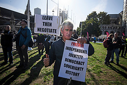 © Licensed to London News Pictures. 19/10/2019. London, UK. A Pro Brexit demonstrator holds up a placard outside The Houses of Parliament in Westminster, London on the day that Parliament will vote on a new agreement between UK government and the EU over Brexit. Parliament is sitting on a Saturday for the first time since 1982. Photo credit: Ben Cawthra/LNP