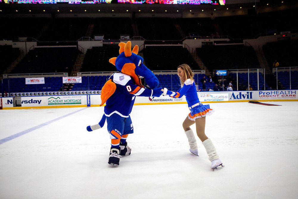 LONG ISLAND, NY - MARCH 28, 2015: New York Islanders mascot Sparky the Dragon spins around with Ice Girl Ashleen Betts during a fan puck shoot after a game between the New York Islanders and the Anaheim Ducks at Nassau Coliseum.