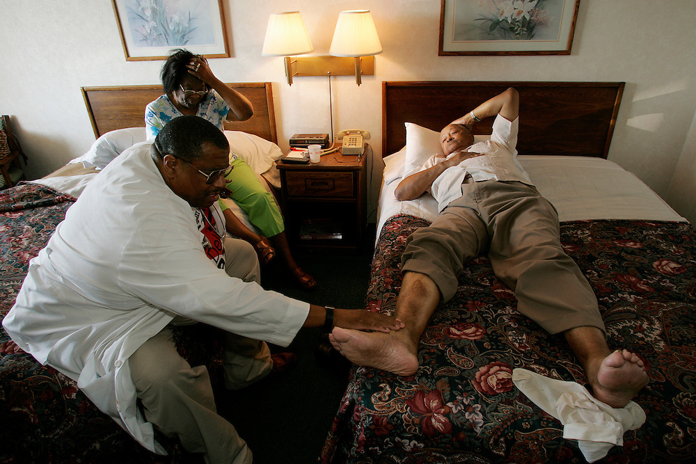 GREENVILLE, MS - September 3, 2005:  Dr. Ronald Myers, dealing with the Hurricane Katrina crisis professionally and personally, checks his injured father-in-law, Leamalie Holmes, 83, while making rounds of Katrina evacuees in Greenville, Mississippi on September 3, 2005. As a doctor and advocate for the poor, he is treating evacuees from New Orleans and other parts of Louisiana and Mississippi in shelters and at homes where the evacuees have taken up residence. His personal home and his in-laws home were severely damaged and all are living in a Ramada Inn...(Photo by Todd Bigelow/Aurora)..