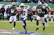 Dec 24, 2017; East Rutherford, NJ, USA; Los Angeles Chargers wide receiver Travis Benjamin (12) is pursued by New York Jets punter Lac Edwards (4) and tight end Eric Tomlinson (83) on a punt return during an NFL football game at MetLife Stadium. The Chargers defeated the Jets 14-7.