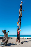 Searching for Reason sculpture on the Malecon in Puerto Vallarta with kids climbing the ladder posing for a photo (sculpture by artist Sergio Bustamante). Model released.