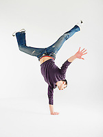 Man doing one handed handstand in studio