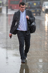 © Licensed to London News Pictures. 26/09/2019. London, UK. A man gets a soaking as he walks past Parliament in a rain shower. Periods of heavy rain have hit parts of the United Kingdom today. Photo credit: Peter Macdiarmid/LNP
