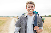 Portrait of happy male hiker with backpack standing on field