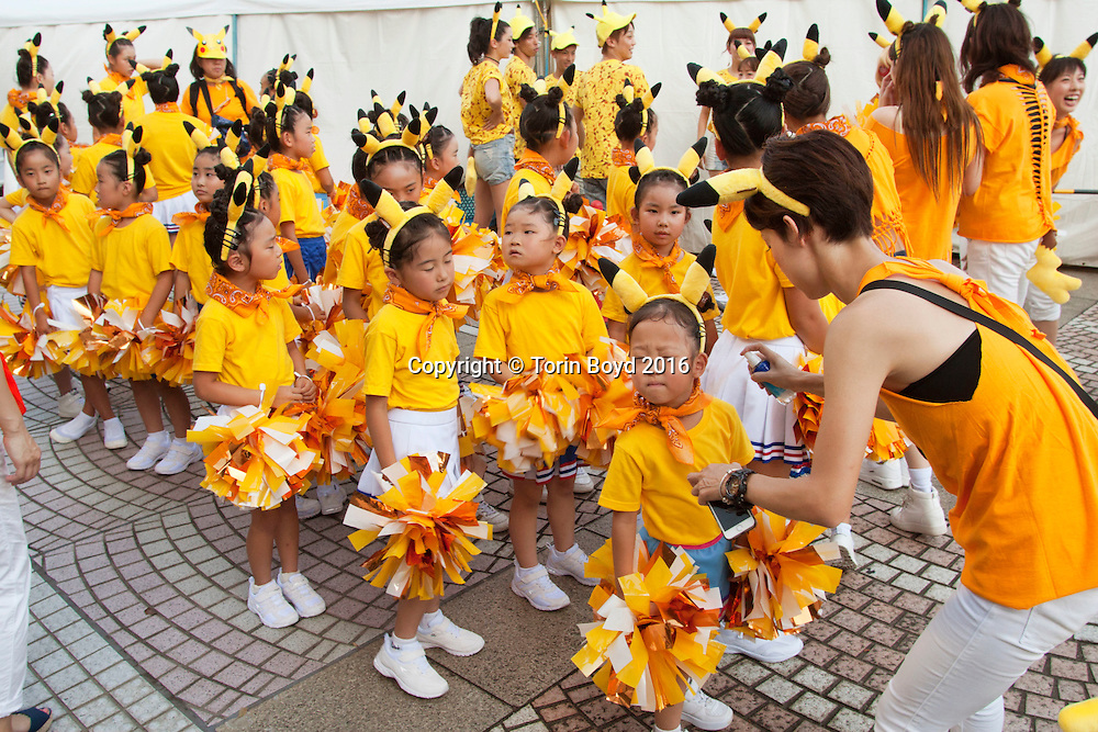 August 7, 2016, Yokohama, Japan: Young cheerleaders participate in the parade of dancing Pikachu mascots, part of Pikachu Outbreak!, a weeklong extravaganza dedicated to Pikachu, the lovable Pokemon character held in Yokohama from August 7 -14, 2016. This annual summer event started in 2014 involves hundreds of Pikachu mascots and huge inflatables making appearances at venues throughout the city's waterfront district known as Minato Mirai. In addition to this parade, other events include a large gathering of Pikachu splashing themselves and fans, a hula dance event, a Pikachu fishing pool, stage performances, Pikachu merchandise for sale and Pikachu photo studios. (Torin Boyd/Polaris).