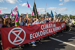 London, UK. 15 July, 2019. Climate activists from Extinction Rebellion cross Waterloo bridge during a march from the Royal Courts of Justice, where they had blocked the road for the day, to a camp site at Waterloo Millennium Green on the first day of the group's 'summer uprising', a series of events intended to apply pressure on local and central government to address the climate and biodiversity crisis.