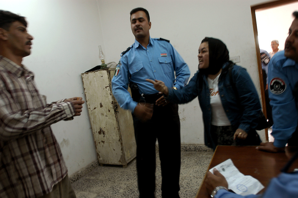 A woman accuses a man after Iraqi police arrested him in the al-Bayaa district police station. As the June 30th handover of sovereignty approaches, the police are under attack by anti-coalition forces and by the Coalition Provisional Authority to take a greater role in providing security..Baghdad, Iraq. 29/04/2004.Photo © J.B. Russell