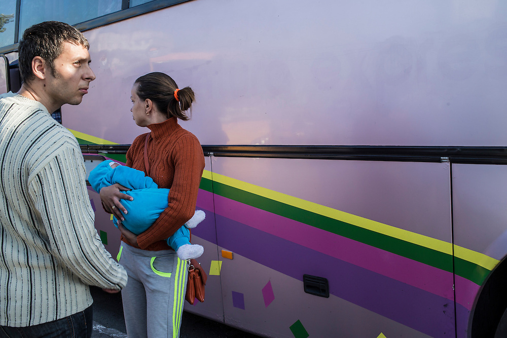 MARIUPOL, UKRAINE - OCTOBER 13: Dmitriy and his wife Anya with their three-month-old daughter stand outside before boarding a bus to the war-torn city of Luhansk on October 13, 2014 in Mariupol, Ukraine. The family left Luhansk two months ago for safety reasons, but lack of work has forced them to return. The United Nations has registered more than 360,000 people who have been forced to leave their homes due to fighting in the East, though the true number is believed to be much higher.(Photo by Brendan Hoffman/Getty Images) *** Local Caption ***