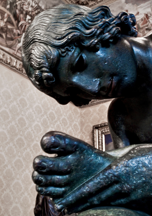 Bronze sculpture of boy with thorn, closeup of head and hand holding his foot