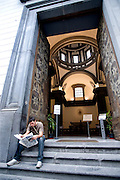 A man reads a newspaper at the entrance to an art museum in Naples.