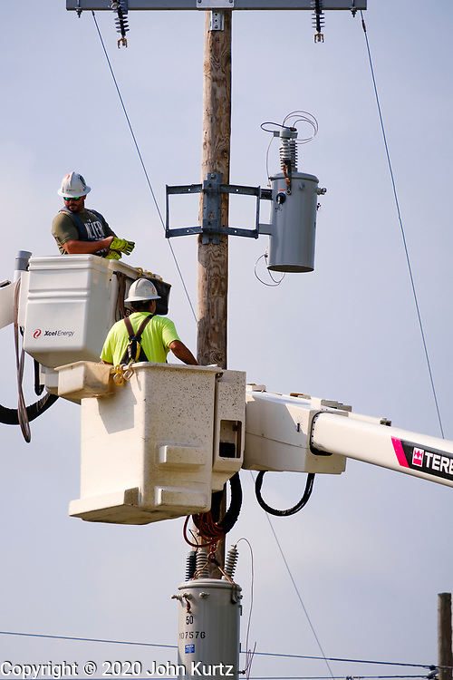 "12 AUGUST 2020 - SLATER, IOWA: A crew from XCel Energy, a Minnesota utility, repair power lines in Slater Wednesday. Power to the town was knocked out in the storm Monday. More than 145,000 Iowans are without power more than 48 hours after the storm. According to Iowa Governor Kim Reynolds, the storm damaged 10 million acres of corn and soybeans in Iowa, about 1 one-third of Iowa's 32 million acres of agricultural land. Justin Glisan, Iowa's state meteorologist, said the storm Monday, Aug. 10, lasted 14 hours and traveled 770 miles through the Midwest before losing strength in Ohio. The storm was a seldom seen ""derecho"" that packed straight line winds of nearly 100MPH. The storm pummelled Midwestern states from Nebraska to Ohio.    PHOTO BY JACK KURTZ"