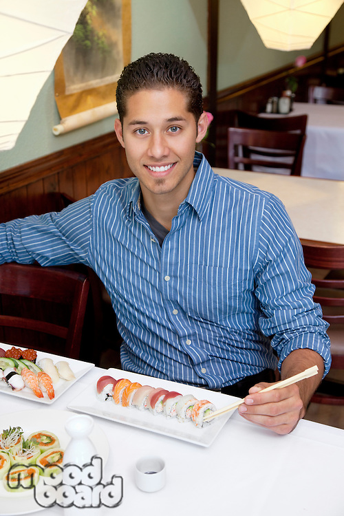 Portrait of a handsome young man eating sushi in Japanese restaurant