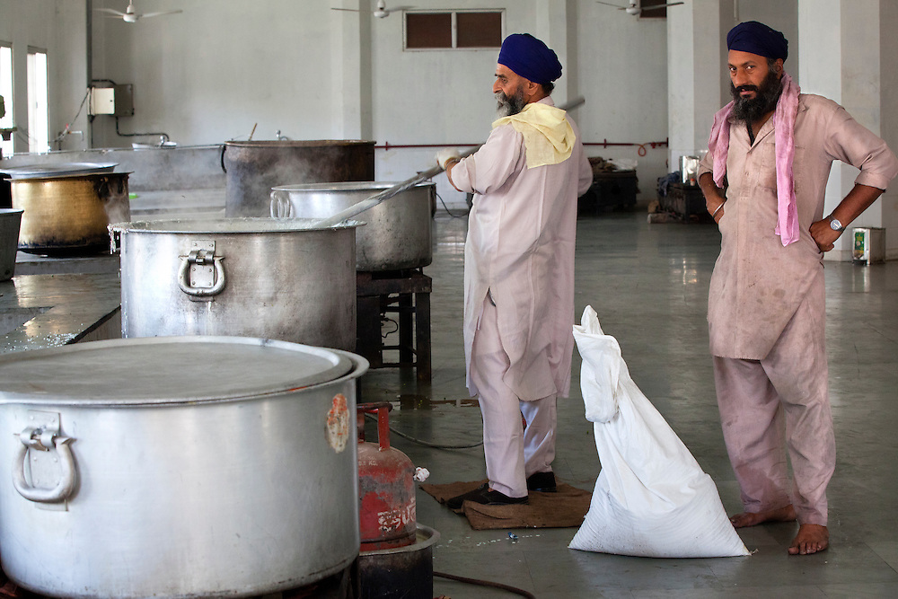 Cooks in a Sikh temple working in the kitchen.The enormous pots are needed to cook for the tens of thousands of pilgrims who come everyday.