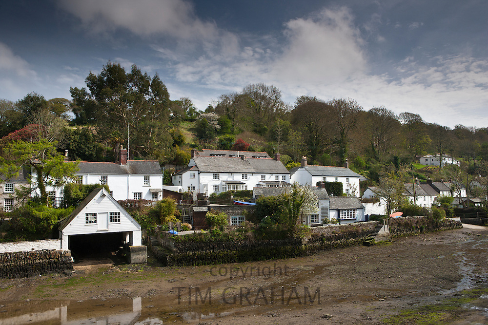 White painted houses in Helston village overlooking the Helford Estuary with the tide out, Cornwall, England, UK