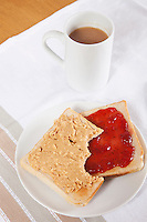 Peanut butter and jam on slices of bread with cup of coffee