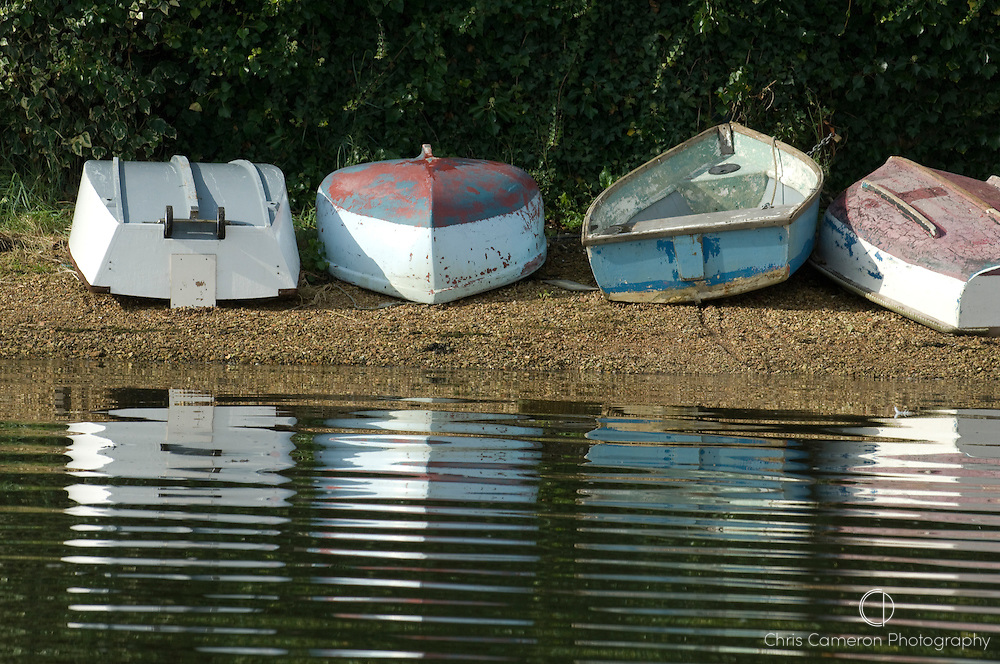 Four dinghies lie on a stoney shore of the Hamble River, Hampshire, England 12/9/2008