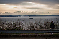 A young lady watches the Washington State Ferry traverse westwards across the Puget Sound with the Olympic Mountains in the background. Typically, small groups of people congregate at this vantage to admire the sunset. (March 22, 2020).