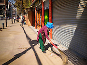 06 MARCH 2017 - KATHMANDU, NEPAL: A woman sweeps the sidewalk in front of a shop in Thamel, the tourist district of Kathmandu.      PHOTO BY JACK KURTZ