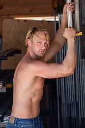 sexy shirtless blond man in a garage