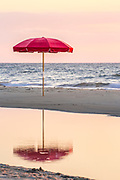Lonely umbrella reflected in a tide pool at a Duck, NC beach on the Outer Banks.
