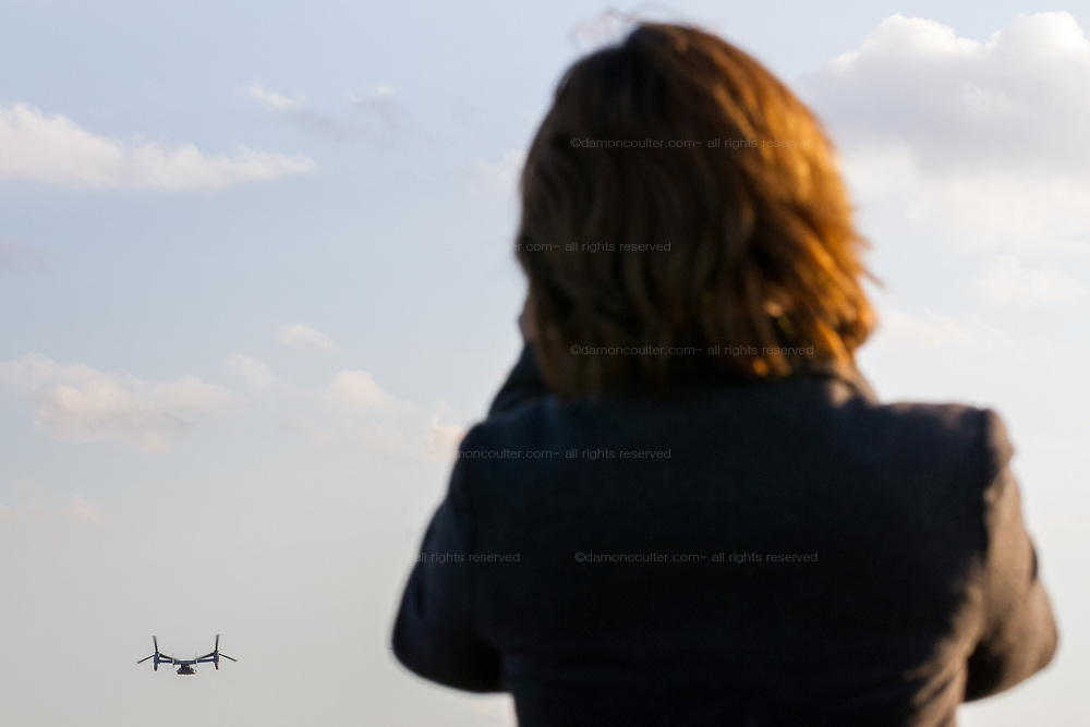 A Japanese woman watches aBell Boeing V22 Osprey tilt-rotor aircraft with the US Marines, taking-off from Naval Air Facility Atsugi in Yamato, Kanagawa, Japan. Friday January 4th 2019. The Osprey is a controversial transport aircraft. With a patchy safety record it is often the focus of anti-US base and forces protests in Japan, especially in Okinawa. It is a rare visitor to this Atsugi Base drawing a crowd of aircraft enthusiasts.