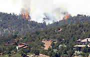 """Fire continues to burn near homes in the Waldo Canyon fire west of Colorado Springs, Colorado June 25, 2012.  A fast-growing wildfire in Colorado forced 11,000 people from their homes at least briefly and threatened popular summer camping grounds beneath Pikes Peak, whose vistas helped inspire the patriotic tune """"America the Beautiful.""""    REUTERS/Rick Wilking (UNITED STATES)"""