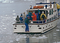 """Passingers aboard charter boat are tasting 5000 year old ice being collected by mate.  Some were putting in their drinks.  Location was at the Holgate Glacier, Alaska.  The floating ice was the result of th the glacier """"calfing""""."""