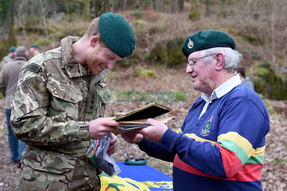February 20, 2019 - Plymouth, United Kingdom - Image licensed to i-Images Picture Agency. 20/02/2019. Plymouth, United Kingdom.  Prince Harry, The Duke of Sussex, Captain General Royal Marines, receives a gift of a rugby shirt and a picture from former Marine Yorkie Malone, during a visit to 42 Commando Royal Marines  in Plymouth, United Kingdom. (Credit Image: © Pool/i-Images via ZUMA Press)
