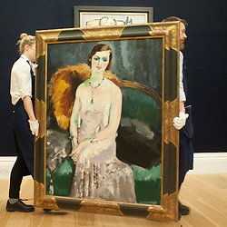 Sotheby's employees transport a painting during the press preview of the forthcoming February sales of Impressionist & Modern Art and Contemporary Art in London, including works by Picasso, Bacon, Monet, Richter, Miró, Basquiat.