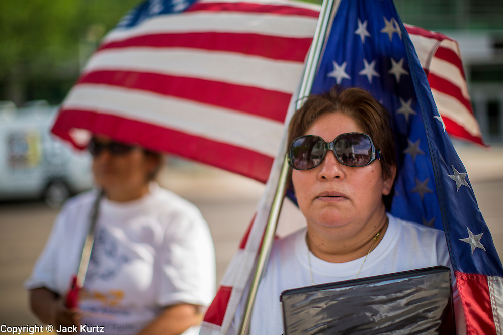 "19 JULY 2012 - PHOENIX, AZ:  PATRICIA ROSAS stands with an American flag in front of the US Courthouse on the first day of a class action lawsuit, Melendres v. Arpaio in Phoenix Thursday. Rosas opposes Arpaio. The suit, brought by the ACLU and MALDEF in federal court against Maricopa County Sheriff Joe Arpaio, alleges a wide spread pattern of racial profiling during Arpaio's ""crime suppression sweeps"" that targeted undocumented immigrants. U.S. District Judge Murray Snow granted the case class action status opening it up to all Latinos stopped by Maricopa County Sheriff's Office deputies during the crime sweeps. The case is being heard in Judge Snow's court.  PHOTO BY JACK KURTZ"