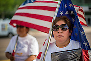 """19 JULY 2012 - PHOENIX, AZ:  PATRICIA ROSAS stands with an American flag in front of the US Courthouse on the first day of a class action lawsuit, Melendres v. Arpaio in Phoenix Thursday. Rosas opposes Arpaio. The suit, brought by the ACLU and MALDEF in federal court against Maricopa County Sheriff Joe Arpaio, alleges a wide spread pattern of racial profiling during Arpaio's """"crime suppression sweeps"""" that targeted undocumented immigrants. U.S. District Judge Murray Snow granted the case class action status opening it up to all Latinos stopped by Maricopa County Sheriff's Office deputies during the crime sweeps. The case is being heard in Judge Snow's court.  PHOTO BY JACK KURTZ"""