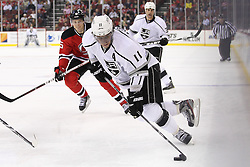 Oct 13; Newark, NJ, USA; Los Angeles Kings center Anze Kopitar (11) skates with the puck by New Jersey Devils defenseman Adam Larsson (5) during the first period at the Prudential Center.