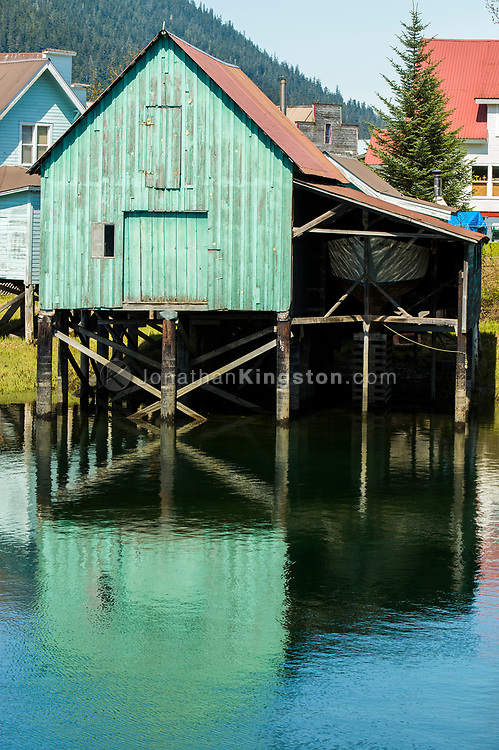 A green building on stilts over water in Petersburg, Alaska.