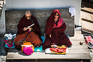 Two monks sit in the shade meditating and reading scriptures at the side of the Boudhanath stupa in Kathmandu, Nepal.