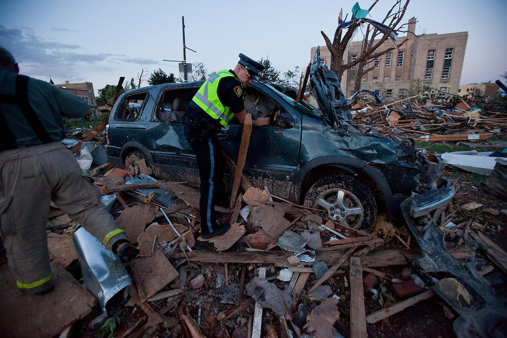Police examine a crushed car after a Tornado caused significant damage to the downtown core of Goderich Ontario, Sunday, August 21, 2011.<br /> THE CANADIAN PRESS/ Geoff Robins