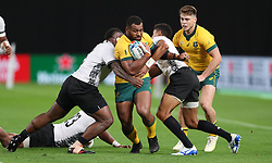 Australia's Samu Kerevi is tackled by Fiji's Viliame Mata and Ben Volavola during the 2019 Rugby World Cup Pool D match at Sapporo Dome.
