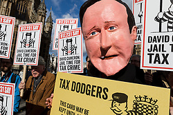 © Licensed to London News Pictures. 25/02/2014. London, UK. Demonstrators, including an actor playing David Cameron protest outside Parliament against tax evasion and for the prosecution of tax dodgers and HSBC officials. The protest takes place just before the Treasury Select Committee hears evidence from HSBC and HMRC bosses on tax evasion this afternoon. Photo credit : Vickie Flores/LNP