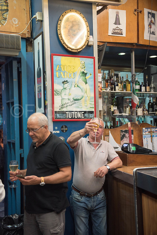 Evening in the Taverna Azzurra at the market of Vucciria, where alcohol flows to rivers in an informality typical of old times