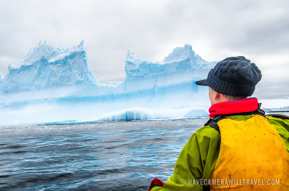 A point-of-view shot of a kayaker paddling amongst large carved icebergs at Melchior Island in Antarctica.