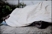 "Swollen hands of a dead body of an heroin abuser. A few days later the man will be removed by the authorities. Rawalpindi, Pakistan, on thursday, November 27 2008.....""Pakistan is one of the countries hardest hits by the narcotics abuse into the world, during the last years it is facing a dramatic crisis as it regards the heroin consumption. The Unodc (United Nations Office on Drugs and Crime) has reported a conspicuous decline in heroin production in Southeast Asia, while damage to a big expansion in Southwest Asia. Pakistan falls under the Golden Crescent, which is one of the two major illicit opium producing centres in Asia, situated in the mountain area at the borderline between Iran, Afghanistan and Pakistan itself. .During the last 20 years drug trafficking is flourishing in the Country. It is the key transit point for Afghan drugs, including heroin, opium, morphine, and hashish, bound for Western countries, the Arab states of the Persian Gulf and Africa..Hashish and heroin seem to be the preferred drugs prevalence among males in the age bracket of 15-45 years, women comprise only 3%. More then 5% of whole country's population (constituted by around 170 milion individuals),  are regular heroin users, this abuse is conspicuous as more of an urban phenomenon. The substance is usually smoked or the smoke is inhaled, while small number of injection cases have begun to emerge in some few areas..Statistics say, drug addicts have six years of education. Heroin has been identified as the drug predominantly responsible for creating unrest in the society."""
